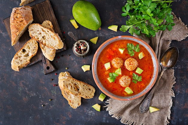Würzige tomatensuppe mit fleischbällchen und gemüse. serviert mit avocado und petersilie. gesundes abendessen. flach lag.