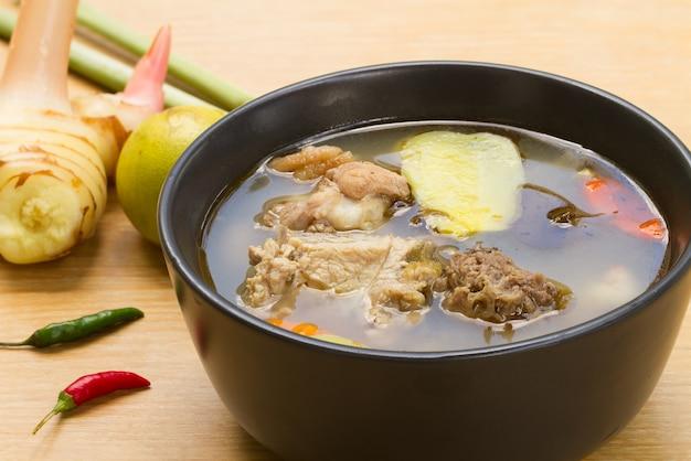 Würzige u. saure suppe mit huhn und jungem tamarindenblatt in einer weißen schale auf einem holztisch.