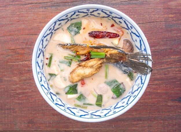 Würzige und saure suppe mit fried fish auf dem holztisch, thailändisches lebensmittel