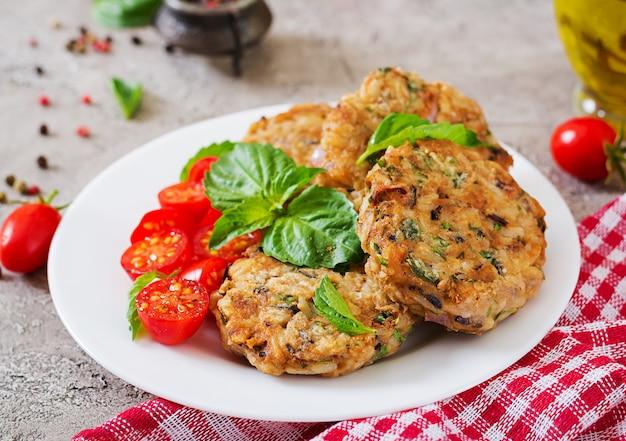 Würzige vegane burger mit reis, kichererbsen und kräutern. salattomate und -basilikum. vegetarisches essen.