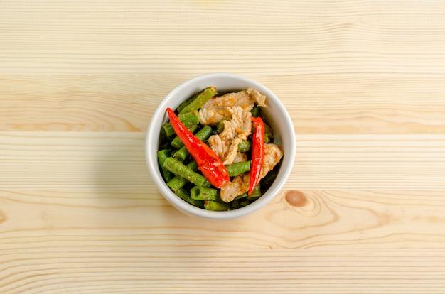 Würziger aufruhr gebratenes schweinefleisch mit roter currypaste und langer bohne yard, thailändisches lebensmittelmenü