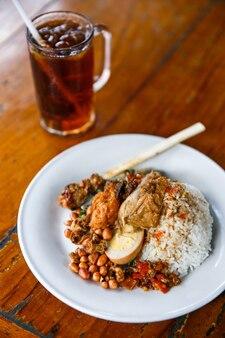 Würziger balinesischer nasi campur mit eistee zum mittagessen