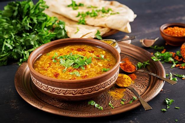 Würziger curry inder dhal in der schüssel, gewürze, kräuter, rustikaler schwarzer hölzerner hintergrund.