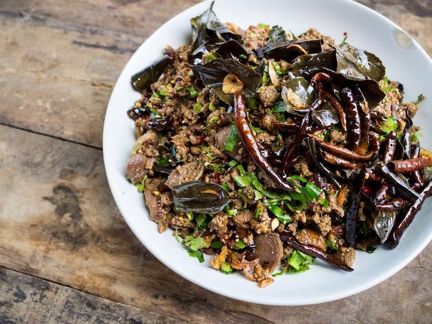 Würziger entensalat mit gemüse und paprikas auf hölzernem hintergrund, thailändische art