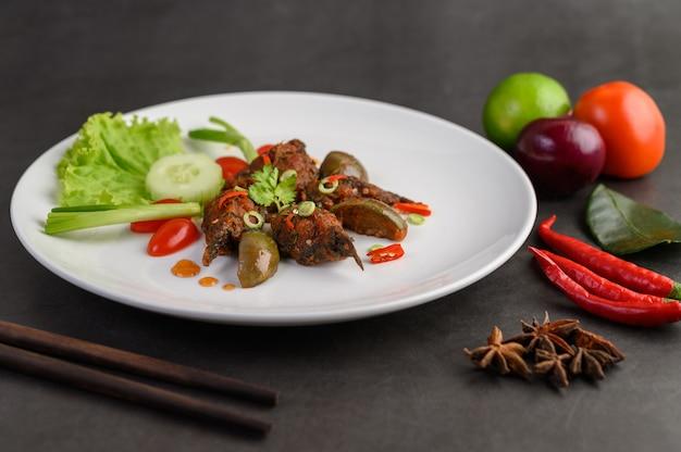 Würziger gebratener rührwels auf weißem teller, thailändisches essen.