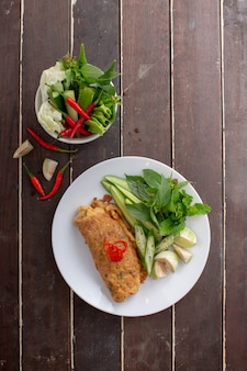 Würziger gehackter schweinefleischsalat eierknödel serviert mit gemüse. thai essen