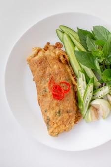 Würziger gehackter schweinefleischsalat eierknödel serviert mit gemüse. thai food isoliert weiß