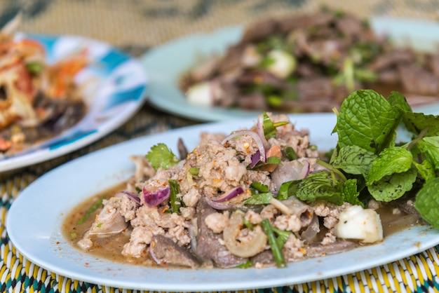 Würziger gehackter schweinefleischsalat oder gemahlener schweinefleischsalat (laab) ist ein thailändisches lebensmittel für gesundheit besteht aus schweinefleisch, grou