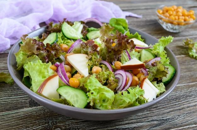 Würziger gesunder salat aus frischem grün, roten zwiebeln, kichererbsen, geräuchertem käse (wurstkäse), gurken in einer schüssel auf einem holztisch. vegetarisches gericht. nahansicht.