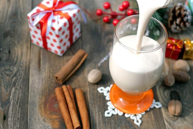 Würziger getränkeierpunsch der vorbereitung selbst gemachter traditioneller weihnachtsmit gemahlener muskatnuss, zimt im glas.