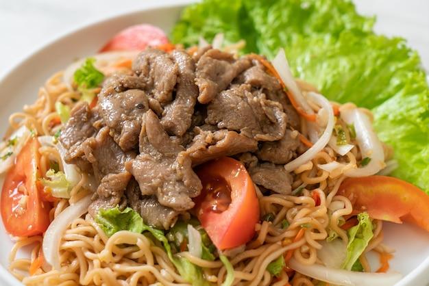 Würziger instant-nudelsalat mit schweinefleisch auf weißem teller - asiatische küche
