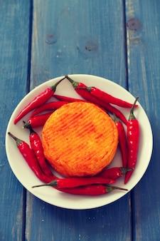 Würziger käse mit rotem pfeffer auf weißer platte auf blauer holzoberfläche
