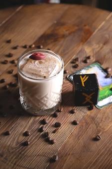 Würziger kaffee-sauer-cocktail mit großem eiswürfel und lippendekor neben den runen in einem mystischen restaurant