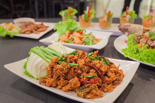 Würziger knuspriger schweinefleischsalat der thailändischen küche, larb mit würzigem lachs- und grillschweinefleisch