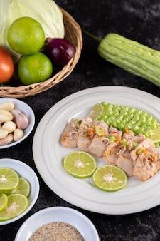 Würziger limetten-schweinefleischsalat mit bitterer melone, galangal, chili, tomaten und knoblauch in einem weißen teller auf einem schwarzen zementboden.