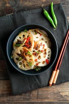 Würziger lotuswurzelsalat auf dem weißen steinhintergrund, asiatisches essen