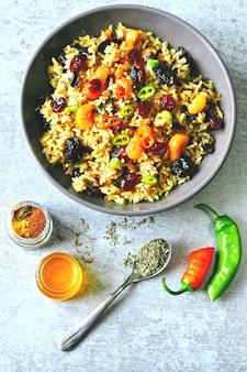 Würziger reis mit getrockneten früchten. vegane schüssel mit würzigem reis. gesundes mittagessen