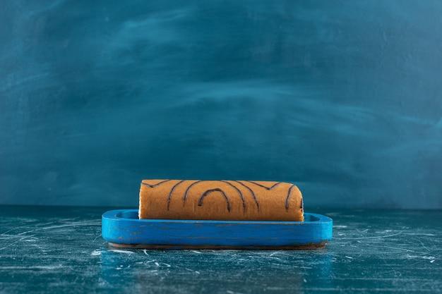 Würziger rollkuchen auf einer holzplatte, auf blauem hintergrund. foto in hoher qualität