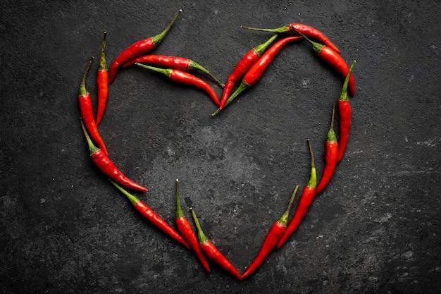 Würziger roter chili in form eines herzens auf dunklem stein