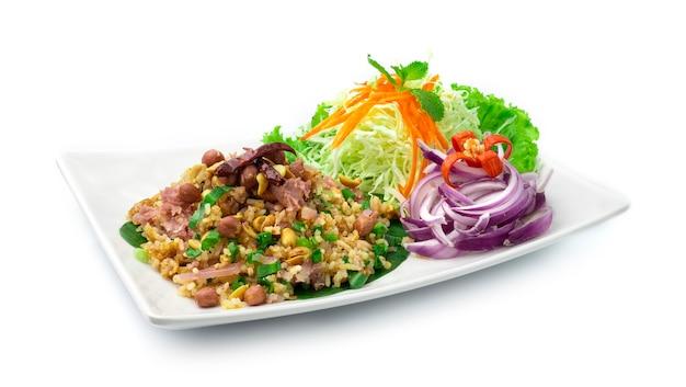 Würziger salat aus curry-reis-kroketten, fermentiertem schweinefleisch-ingwer und erdnüssen