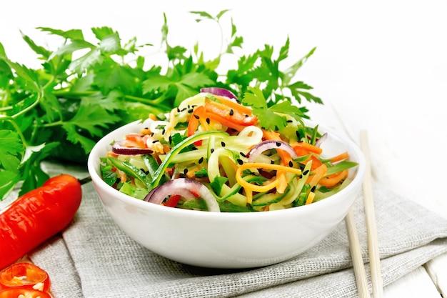 Würziger salat aus gurken, karotten, chilischoten, lila zwiebeln, koriander und schwarzem sesam, gewürzt mit essig und zitronensaft in einer schüssel auf einem handtuch auf holzbretthintergrund Premium Fotos