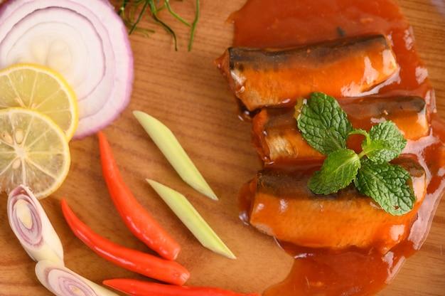Würziger salat der sardine in der tomatensauce auf hölzernem behälter