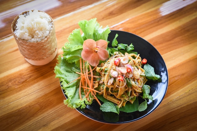 Würziger salat des thailändischen bambussprosses diente auf platte auf der trockenen suppe des holztischs und des kitzigen reis bambussprosses.