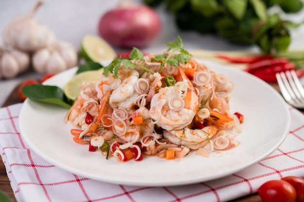 Würziger salat mit garnelen auf einem weißen teller. thai essen.