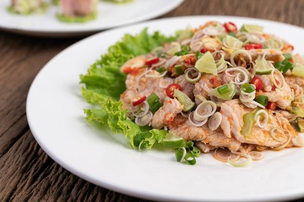 Würziger schweinefleischsalat mit galangal, zitrone, chili, knoblauch und salat auf einen weißen teller geben.