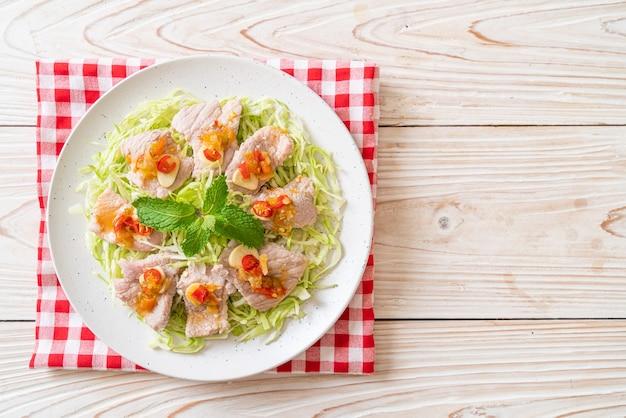 Würziger schweinefleischsalat oder gekochtes schweinefleisch mit limetten-knoblauch-chili-sauce