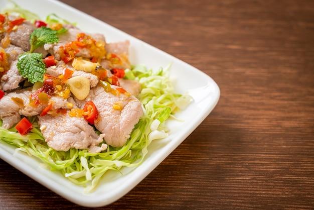 Würziger schweinesalat oder gekochtes schweinefleisch mit limetten-knoblauch-chili-sauce