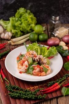 Würziger tintenfisch-garnelen-salat in weißer schüssel mit zitronen-koriander und salat