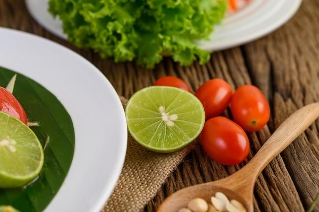 Würziges essen nach thailändischer art, som tum-lebensmittelkonzept, requisitendekoration knoblauch, zitrone, erdnüsse, tomaten und salat auf holztisch.