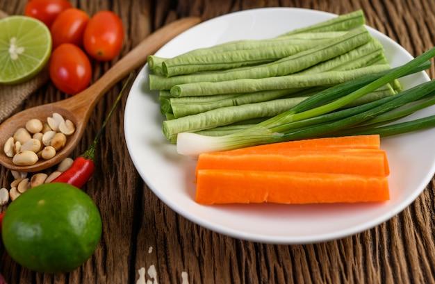 Würziges essen nach thailändischer art, som tum-lebensmittelkonzept, requisitendekoration knoblauch, zitrone, tomaten, chili, lang geschlüpfte bohnen, frühlingszwiebeln, schalotten sowie karotten und erdnüsse auf holzlöffel auf holztisch.