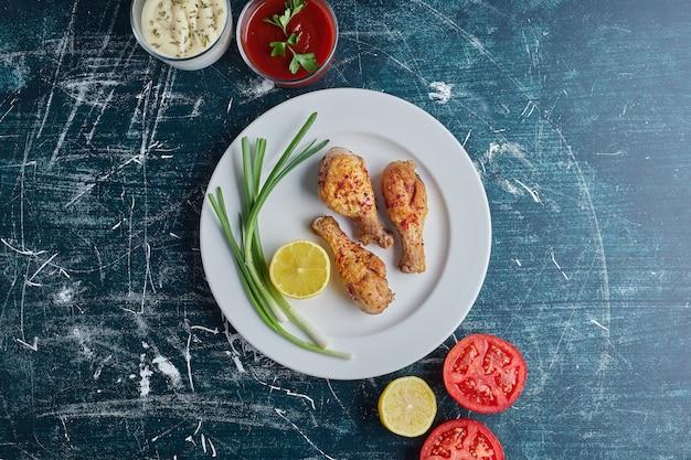 Würziges hühnerfleisch in einem weißen teller mit zutaten herum.