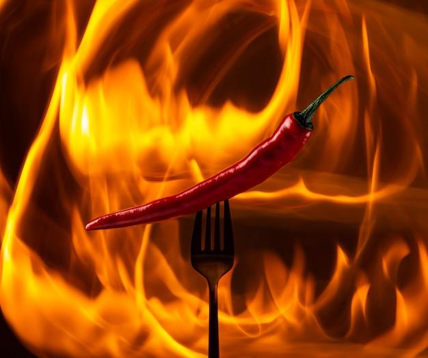 Würziges rotes dampfendes chili auf einer schwarzen gabel auf einem feurigen hintergrund. kunst.