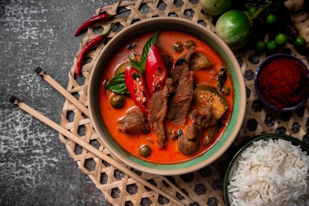 Würziges rotes schweinefleisch-curry mit jasminreis und curry-paste auf einem holzteller - thai-beilage