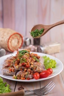 Würziges schweinefleisch mit tomaten und salat auf einem weißen teller auf einem holztisch gehackt.