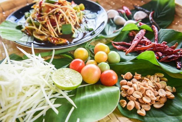 Würziges thailändisches lebensmittel des grünen papayasalats mit kräutern und gewürzbestandteilen mit paprikatomatenerdnuss