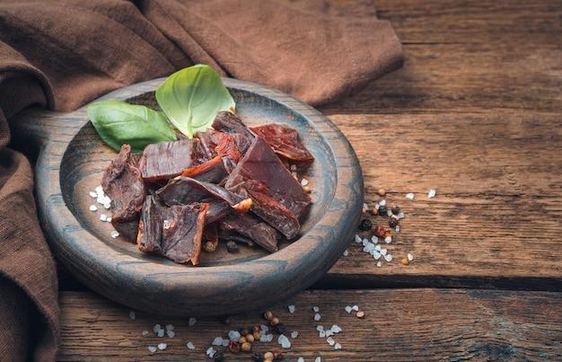 Würziges trockenfleisch mit pfeffer, salz auf braunem naturhintergrund.
