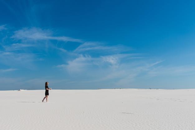 Wüste mit weißem sand und frau im schwarzen kleid