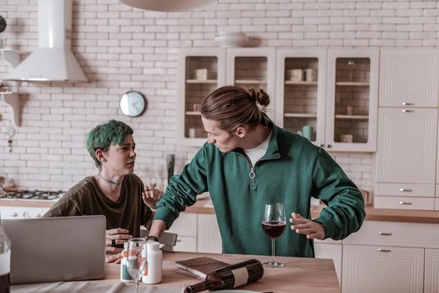Wütend auf frau. blonder ehemann, der ein grünes hemd trägt und wütend auf seine frau ist, die allein alkohol trinkt
