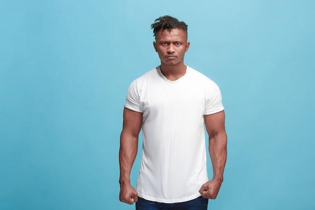 Wütend, hass, wut. emotionaler verärgerter afro-mann auf blauem studiohintergrund. emotionales, junges gesicht. vorderes männliches porträt in halber länge. menschliche emotionen, gesichtsausdruckkonzept. trendige farben