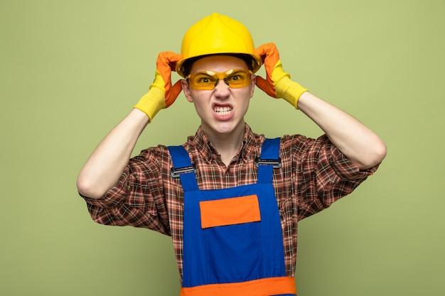 Wütend mit den händen um den kopf junger männlicher baumeister, der uniform und handschuhe mit brille trägt