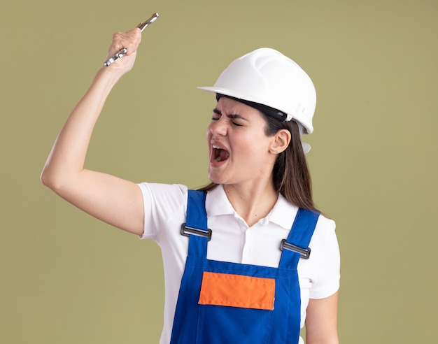 Wütend mit geschlossenen augen junge baumeisterfrau in uniform, die den offenen schraubenschlüssel hält, der auf olivgrüner wand lokalisiert wird
