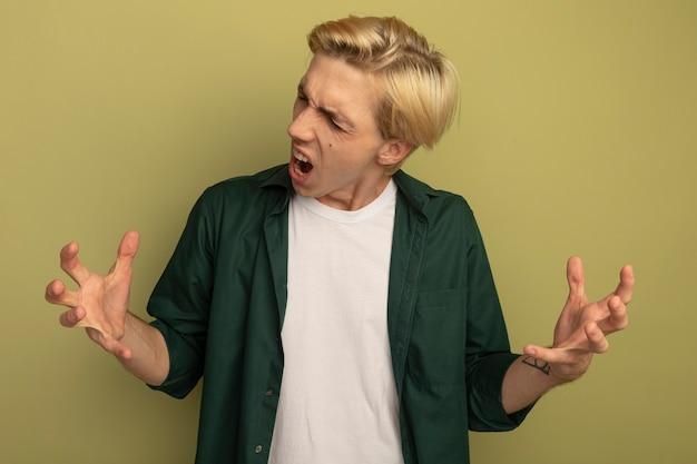 Wütend mit geschlossenen augen junger blonder kerl, der grünes t-shirt trägt, das hände ausbreitet