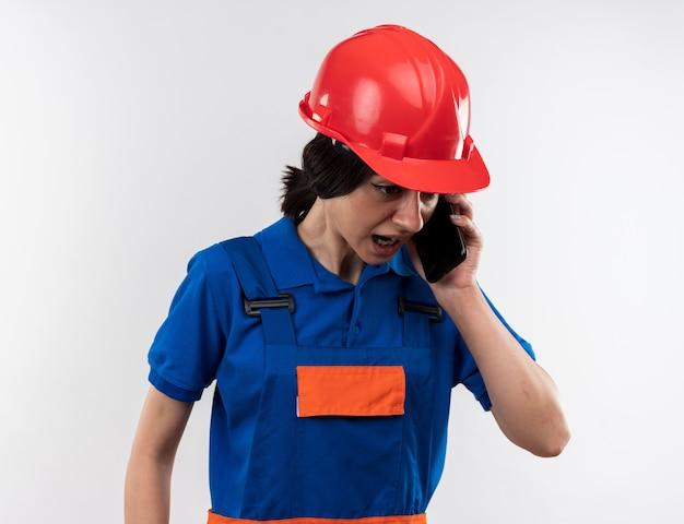 Wütend nach unten schauende junge baumeisterin in uniform spricht am telefon