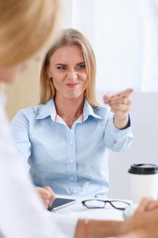 Wütend schreiender boss zeigt auf den arm, um die entlassung zu beenden