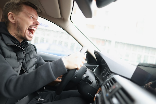 Wütend schreiender männlicher fahrer, der auto nahaufnahme fährt