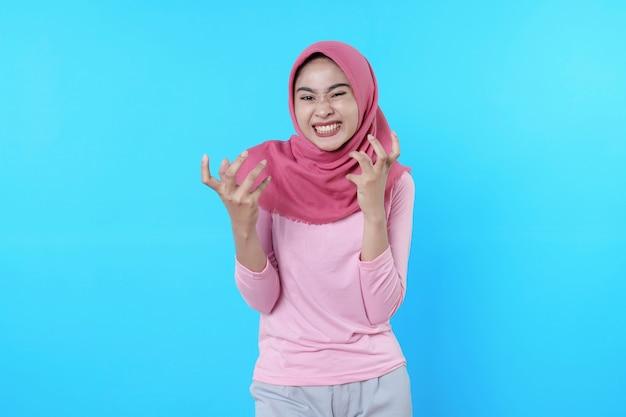 Wütend schreiendes asiatisches frauenporträt isoliert auf blauem hintergrund mit hijab und rosa t-shirt